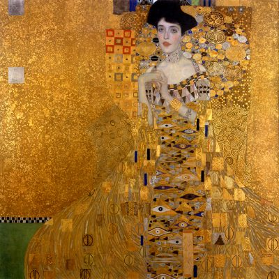 Gustav Klimt's The Woman In Gold, a portrait with a fair woman with black hair. She is delicately poising her hands and is surrounded by a complex gold pattern.
